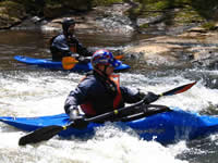 Paddlers play in the rapids after the race © Rebekah Guss